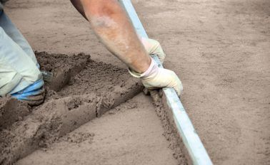 Screeding a floor and levelling it with a tamping screed bar